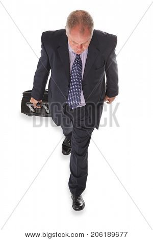 Overhead photo of a businessman in a suit pulling a travelling suitcase, isolated on a white background.
