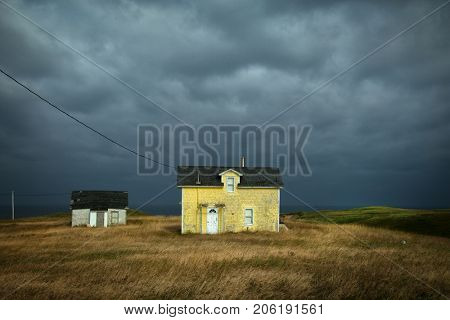 Old fisherman house with yellow tiles in a dark grey sky in iles de la madeleine in Canada