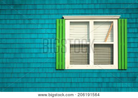 Traditional window with neon green shutters on a dark turquoise wooden tiles wall in Iles de la Madeleine in Quebec, Canada