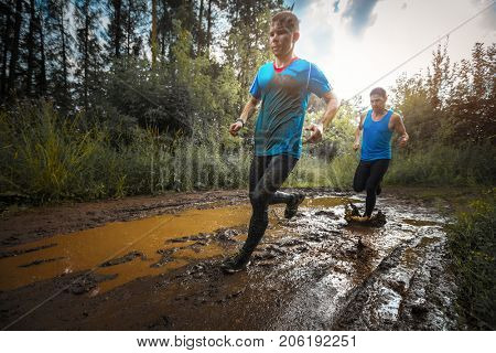 Two sporty men run on the wild rural muddy road