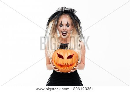 Crazy smiling woman dressed in black widow costume holding halloween pumpkin isolated over white background