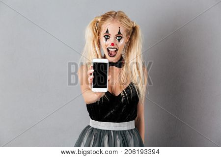 Portrait of an excited blonde woman in halloween clown make-up showing blank screen mobile phone isolated over gray background
