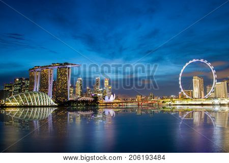 SINGAPORE - SEPTEMBER 8, 2017: Singapore skyline at Marina Bay during sunset blue hour showing Marina Bay Sands, Gardens by the Bay and Singapore Flyer ferris wheel.