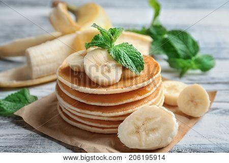Yummy banana pancakes on wooden table