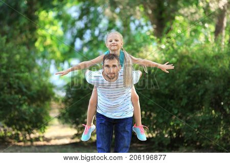 Young man playing with little girl in park