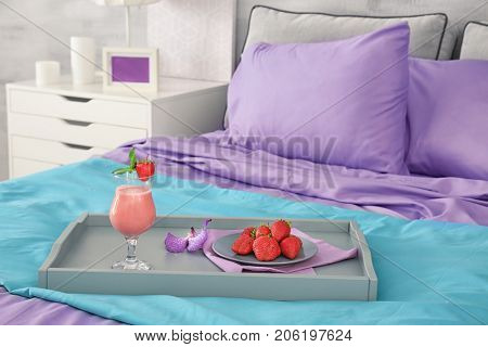 Lilac accent in modern interior. Tray with tasty breakfast on bed