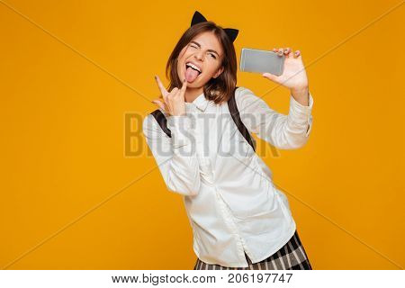 Funny teenage schoolgirl in uniform with backpack taking a selfie while standing and showing rock gesture isolated over orange background