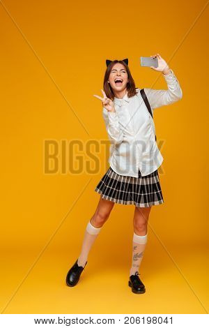 Full length portrait of a happy teenage schoolgirl in uniform with backpack taking a selfie while standing and winking isolated over orange background