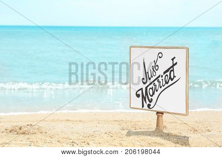 Wooden board with text JUST MARRIED on seaside. Beach wedding concept