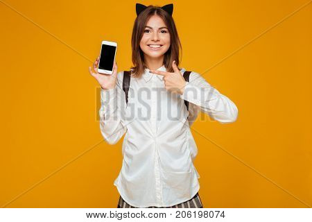 Happy teenage schoolgirl in uniform with backpack pointing finger at blank screen mobile phone isolated over orange background