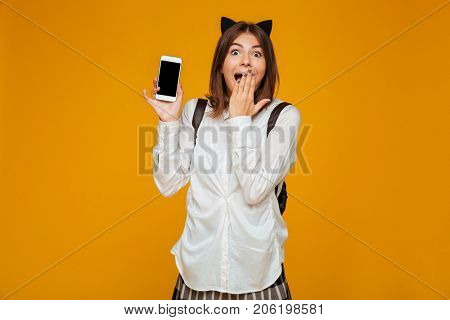 Young excited teenage schoolgirl in uniform with backpack standing and showing blank screen mobile phone isolated over orange background