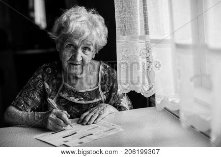 Elderly woman fills out a payment slip. Black-and-white portrait.