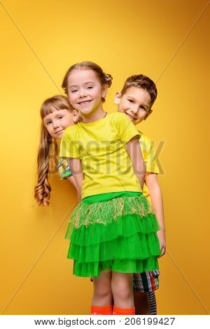 Happy joyful children having fun together. Children's fashion. Education. Happiness, activity and child concept. Bright yellow background.