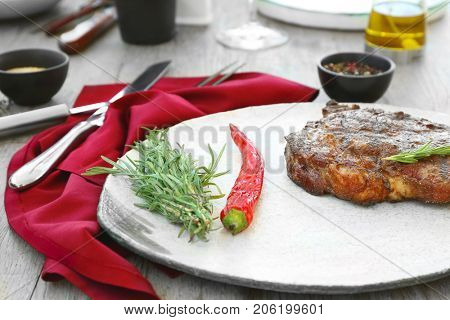 Delicious steak served with rosemary and chili pepper on serving board