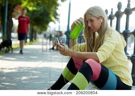 Pretty blonde woman resting outdoors, using mobilephone.