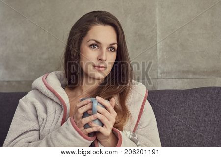 Beautiful young woman drinking tea at home at wintertime.