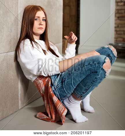Bored young casual girl squatting at home by wall.