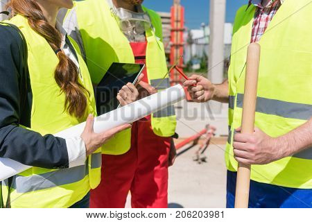 Side view close-up of a female architect or engineer holding a rolled blueprint, while talking with the workers about the implementation of the construction plan