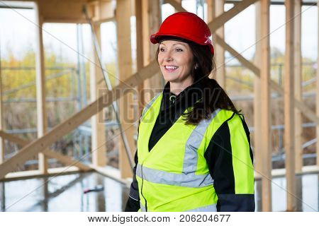 Thoughtful Female Carpenter In Protective Wear At Site