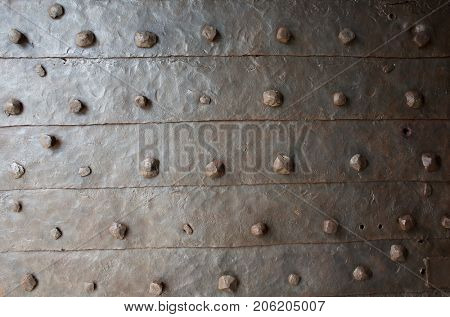 old rusty forged metal with rivets texture
