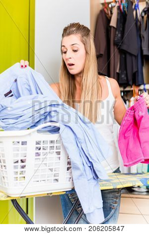 young Woman in front of wardrobe in bedroom folding laundry