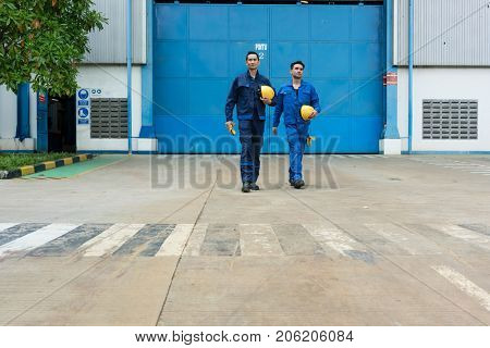 Two Asian workers wearing blue uniforms while walking out from factory after work