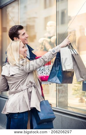 Couple at shop window doing Christmas shopping, man and woman
