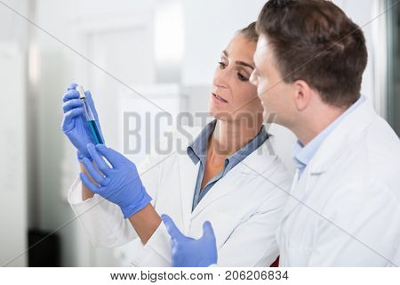 Scientists in laboratory looking at blue liquid in vial for experiment or test