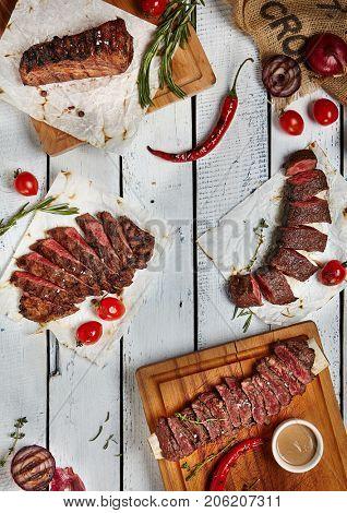 Gourmet Grill Restaurant Steak Menu - Various Grilled Beef Steak on Wooden Background. Black Angus Beef Steak. Beef Steak Dinner. Top VIew