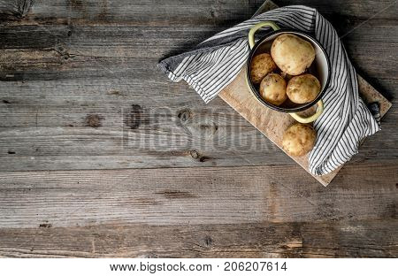 Delicious young potatoes sitting on a cutting board, blue and white napkin, topview