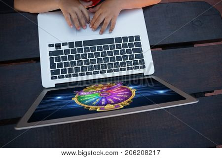 Wheel of fortune on mobile screen against overhead view of boy using digital laptop while sitting at table
