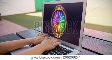 Colorful wheel of fortune on mobile screen against close up of boy using digital laptop while sitting at table