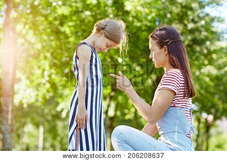 Strict mother talking to her naughty daughter in park