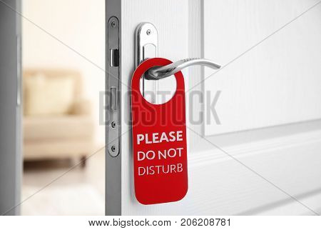 Open door with sign PLEASE DO NOT DISTURB on handle at hotel