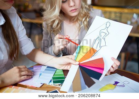 Two fashion designers choosing color for new model of dress from pantone chart