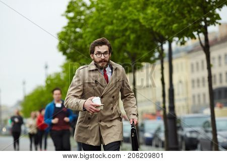 Busy man in elegant trench-coat carrying drink and briefcase while running for work after coffee-break