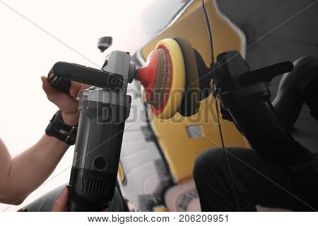 Man polishing car with power buffer machine in repair shop