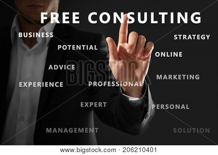 Man working with virtual screen on dark background. Consulting service concept