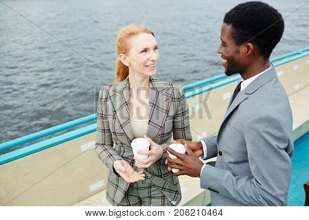 Intercultural colleagues with drinks consulting during outdoor meeting on steamship board