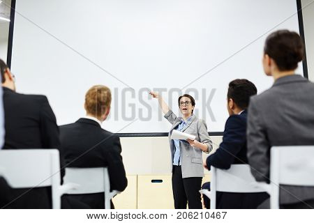 Intelligent businesswoman explaining her audience methods of financial increase, income and prosperity