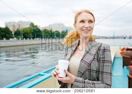 Happy middle-aged woan with drink enjoying cruise on steamship