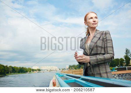 Serene businesswoman with drink enjoying solitude on steamer by riverside