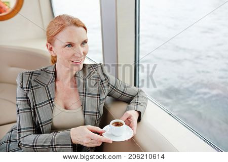 Middle aged businesswoman with cup of coffee looking through window of steamship during travel