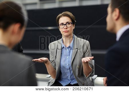 Unsure businesswoman with open palms looking at one of colleagues during conversation