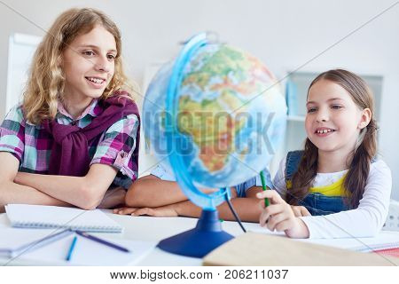 Two classmates looking at globe model and discussing lands
