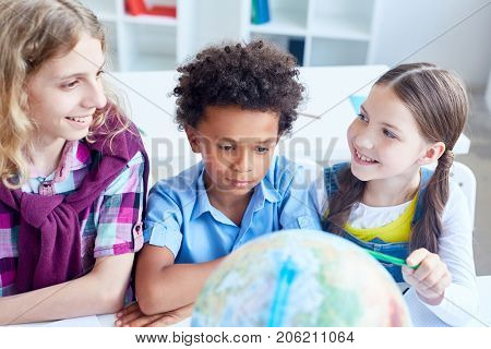 Clever girl pointing at globe model and looking at her classmates
