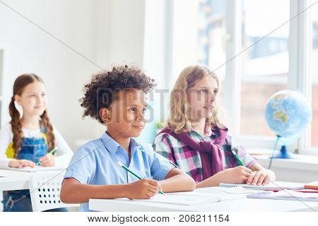 Clever classmates looking attentively at blackboard at lesson