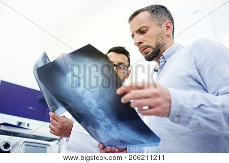 Radiologist explaining patient the problem of his spinal column on x-ray image
