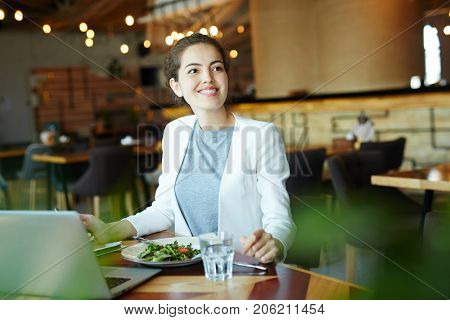 Attractive young financial manager with charming smile looking away while preparing annual accounts on laptop and enjoying delicious lunch at modern restaurant, waist-up portrait