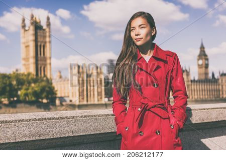 London fashion model in autumn trench coat. Asian woman wearing stylish red fall jacket visiting Westminster and Big Ben, Europe traveler.